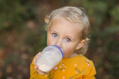 Portrait of blond toddler girl with blue eyes drinking milk from a bottle - NMSF00392