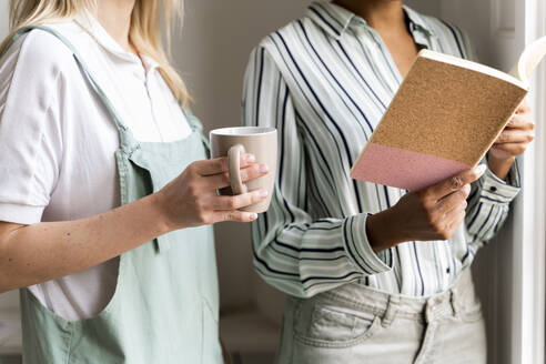 Cropped view of two women with notebook and cup of coffee - AFVF04758