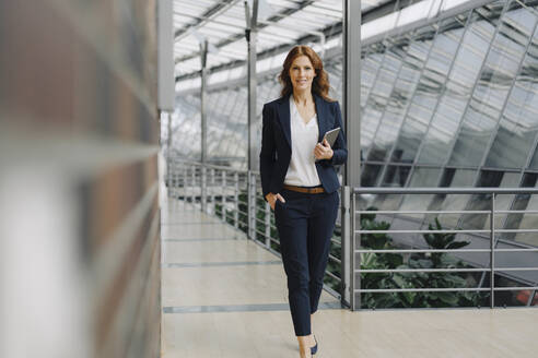 Confident businesswoman holding a tablet in a modern office building - JOSF04142