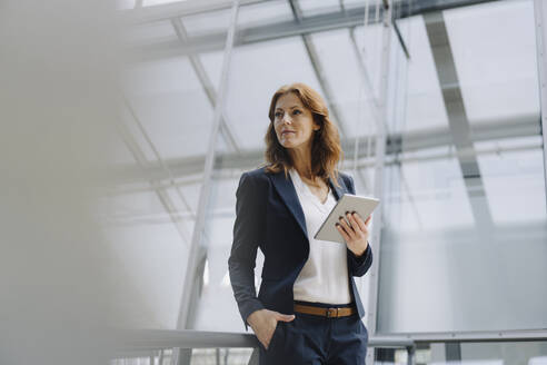 Confident businesswoman holding a tablet in a modern office building - JOSF04145