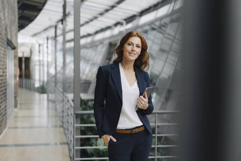Confident businesswoman holding a tablet in a modern office building - JOSF04148