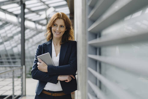 Portrait of a smiling businesswoman holding a tablet in a modern office building - JOSF04154
