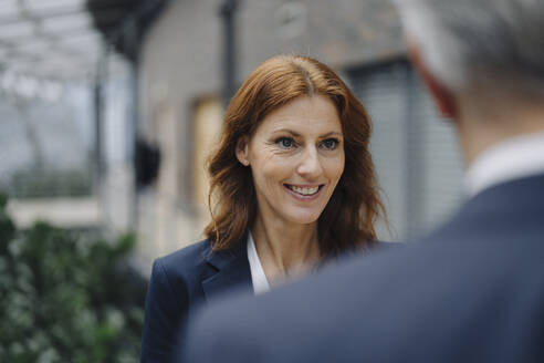 Portrait of smiling businesswoman talking to businessman in office - JOSF04160