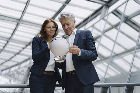 Businessman and businesswoman looking at globe in modern office building - JOSF04163