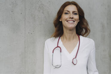 Portrait of a smiling female doctor at a concrete wall - JOSF04169