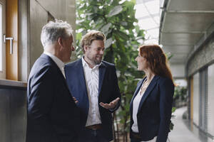 Smiling business people talking in modern office building - JOSF04178
