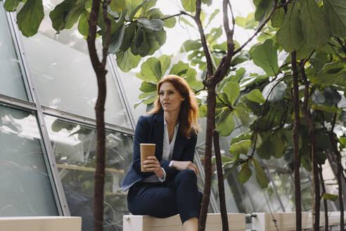Businesswoman having a break in a modern office building - JOSF04181