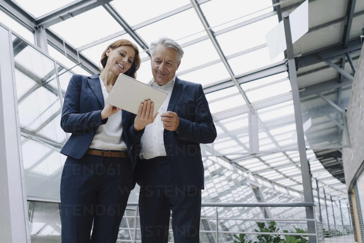 Smiling businessman and businesswoman using tablet in modern office building - JOSF04202 - Joseffson/Westend61