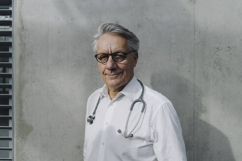 Portrait of a confident senior doctor at a concrete wall - JOSF04205