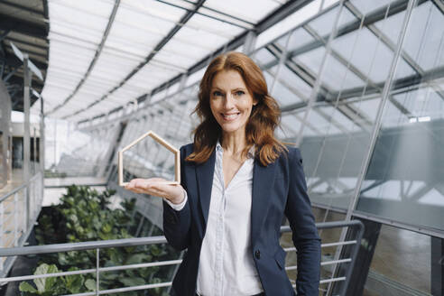 Portait of a confident businesswoman holding a house model in office - JOSF04214