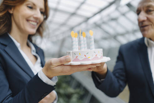 Businessman and businesswoman celebrating birthday in office with fake birthday cake - JOSF04217