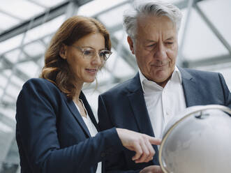 Businessman and businesswoman looking at globe in office - JOSF04226