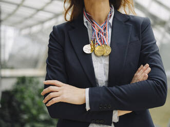 Close-up of businesswoman wearing medals around her neck in office - JOSF04235