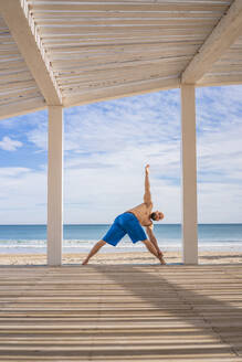 Sportsman training at the beach, triangle pose - DLTSF00382