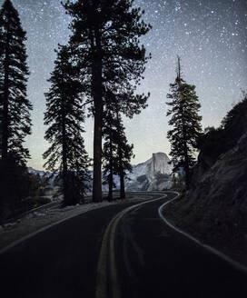 Road passing by silhouette trees in Yosemite National Park against stary sky at night - CAVF72518