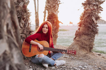 Portrait of young woman playing guitar on the beach, Almunecar, Spain - LJF01213