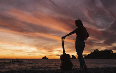 Silhouette of woman with guitar standing on the beach at sunset, Almunecar, Spain - LJF01216