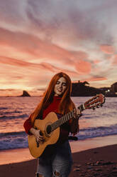 Portrait of redheaded young woman playing guitar on the beach at sunset, Almunecar, Spain - LJF01219