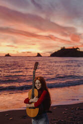 Portrait of redheaded young woman embracing guitar on the beach at sunset, Almunecar, Spain - LJF01222