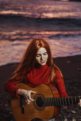 Portrait of redheaded young woman playing guitar on the beach at sunset, Almunecar, Spain - LJF01225