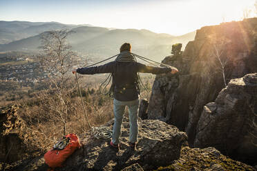 Female climber with rope standing on Battert rock at sunset, Baden-Baden, Germany - MSUF00108