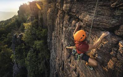 Man climbing Battert rock at sunset, Baden-Baden, Germany - MSUF00117