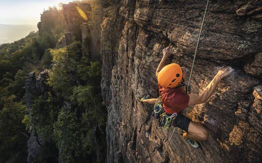 Man climbing Battert rock at sunset, Baden-Baden, Germany - MSUF00117