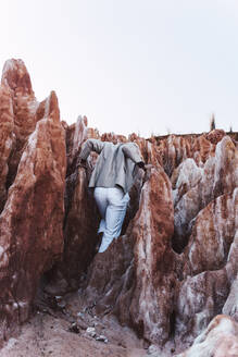 Rear view of young man climbing on rocks - ERRF02422