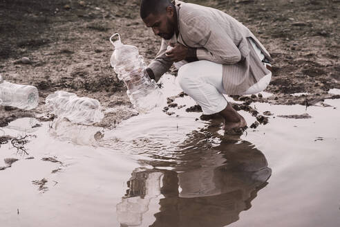 Young man filling plastic bottle with water at a water hole - ERRF02506