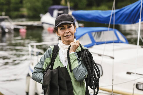 Portrait of confident female instructor holding rope and life jackets against yacht during boat master course - MASF15998