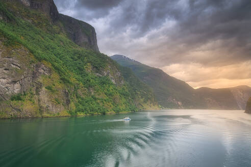 Small boat sailing in the amazing Norway fjords at sunset - CAVF72563