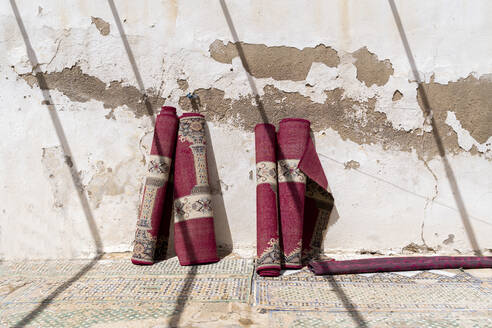 Four rolled up carpets leaning against wall at sunlight, Fez, Morocco - AFVF04807