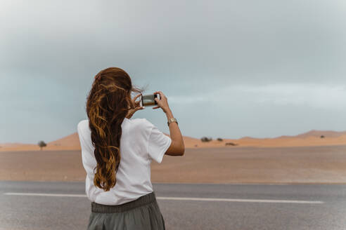 Back view of young woman standing  roadside taking photo with smartphone, Fez, Morocco - AFVF04828