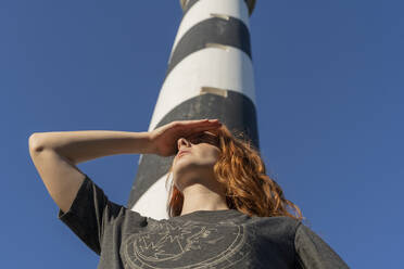 Redheaded young woman at a lighthouse looking out - AFVF04853