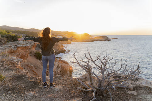 Redheaded young woman standing at the coast at sunset, Ibiza, Spain - AFVF04862