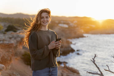 Portrait of smiling redheaded young woman with cell phone at the coast at sunset, Ibiza, Spain - AFVF04865