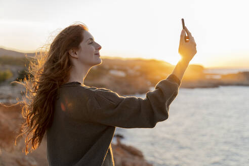 Redheaded young woman taking a selfie at the coast at sunset, Ibiza, Spain - AFVF04868