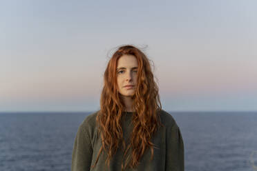 Portrait of redheaded young woman at the coast at sunset, Ibiza, Spain - AFVF04871