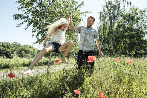 Father with daughter jumping in poppy meadow - WFF00244