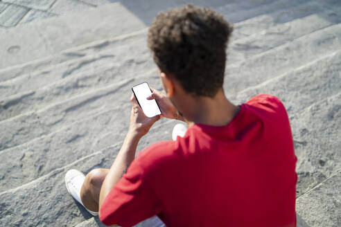 Young man sitting on outdoor stairs checking his smartphone - FBAF01139