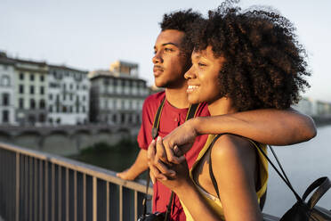 Happy young tourist couple on a bridge above river Arno at sunset, Florence, Italy - FBAF01163