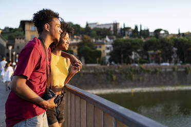 Happy young tourist couple on a bridge above river Arno at sunset, Florence, Italy - FBAF01166
