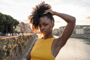 Portrait of a confident young woman at river Arno at sunset, Florence, Italy - FBAF01172