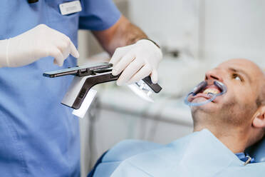 Close-up of dentist taking photo of dentures with special photographic apparatus - OCMF00973