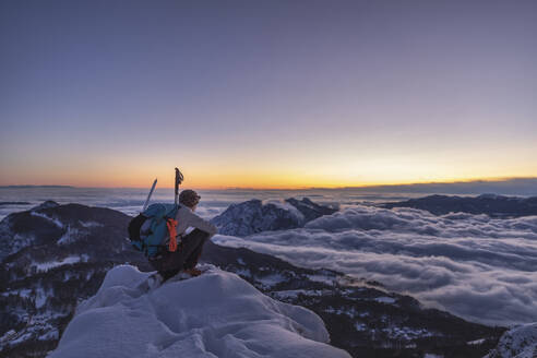 Mountaineer on the mountain summit during twilight, Orobie Alps, Lecco, Italy - MCVF00169