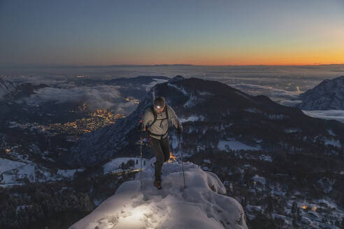 Mountaineer on the mountain summit during twilight, Orobie Alps, Lecco, Italy - MCVF00172