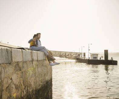 Young couple sitting on pier at the waterfront enjoying the view, Lisbon, Portugal - UUF19814