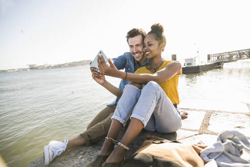 Happy young couple sitting on pier at the waterfront taking a selfie, Lisbon, Portugal - UUF19820