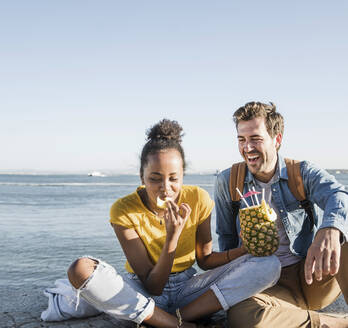 Happy young couple sitting on pier at the waterfront with a pineapple, Lisbon, Portugal - UUF19850