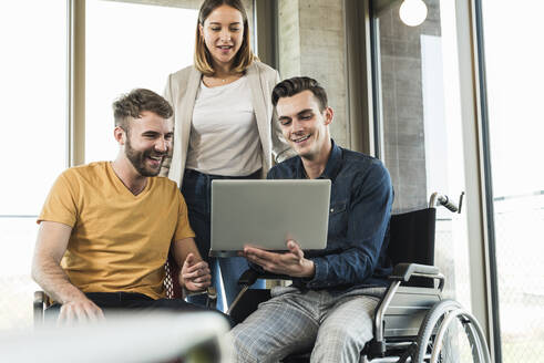 Young businessman in wheelchair showing laptop to colleagues in office - UUF19886